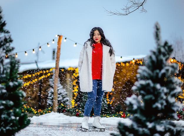赤い冬のセーターとアイスリンクでポーズをとる白いコートの長いブルネットの髪を持つかなり若いアジアの女性