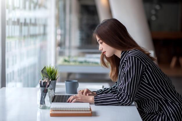 Довольно молодая азиатская женщина работая на столе с компьтер-книжкой в современном офисе.