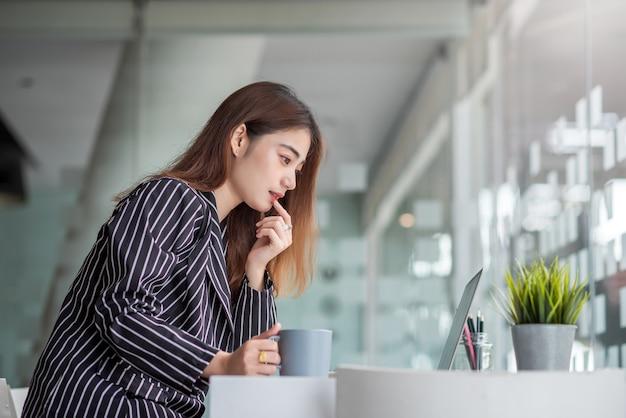 現代のオフィスでラップトップを持って机で働くかなり若いアジアの女性。