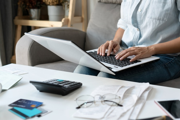 Pretty young asian woman working with computer laptop to do home expenses and taxes in living room at home.
