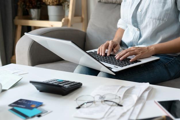 かなり若いアジアの女性が自宅の居間で家の費用と税金を行うためにコンピューターのラップトップで働いています。