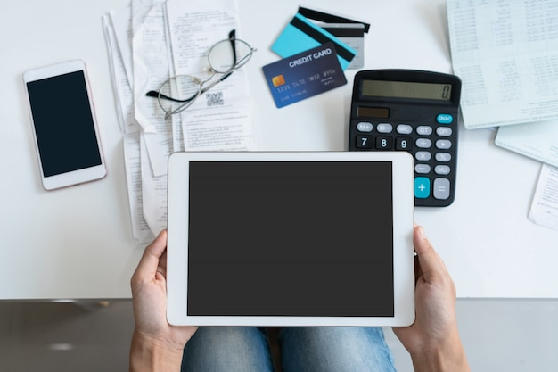 Pretty young asian woman working with tablet to do home expenses and taxes in living room at home. copy space, top view.