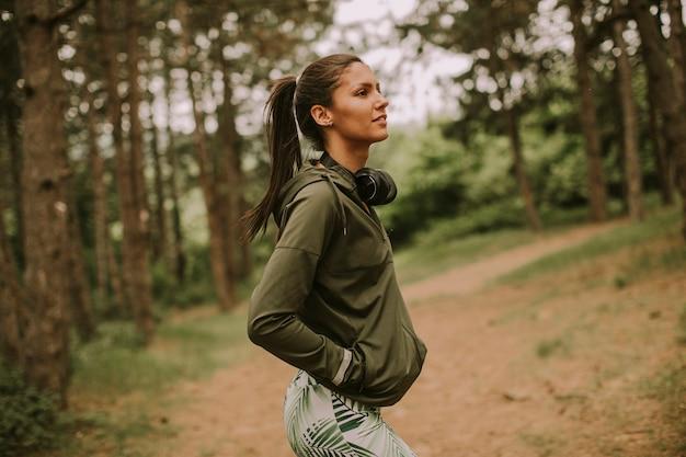 音楽を聴き、森でジョギングした後休憩するかなり若い魅力的な女性ランナー