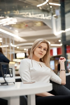 Pretty young beautiful blonde woman with long hair, sitting in cafe in mall. attractive modern girl in trendy clothes is enjoys hot drink indoors.