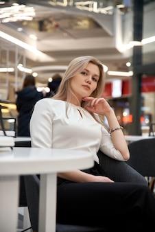 쇼핑몰에서 카페에 앉아 긴 머리를 가진 꽤 젊은 아름 다운 금발 여자. 최신 유행의 옷을 입고 매력적인 현대 소녀는 실내에서 뜨거운 음료를 즐깁니다.
