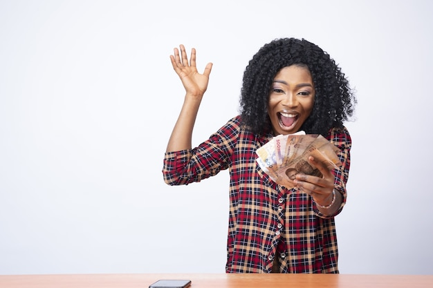 Pretty young black lady holding money and celebrating in front of a white background