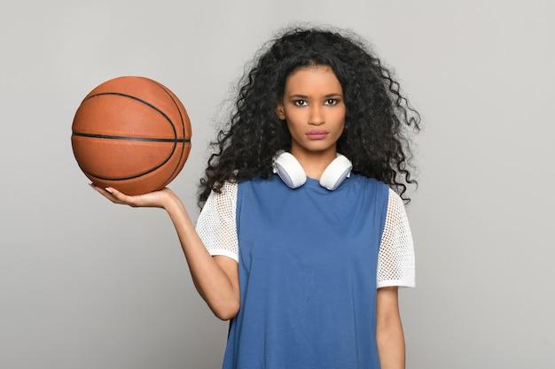 꽤 젊은 흑인 여성이 손에 농구공을 들고 진지한 표정을 하고 목에 헤드폰을 낀 채 카메라를 쳐다보며 포즈를 취하고 있다 프리미엄 사진