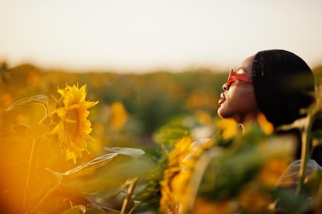 Довольно молодая черная женщина носить летнее платье позы в поле подсолнечника.