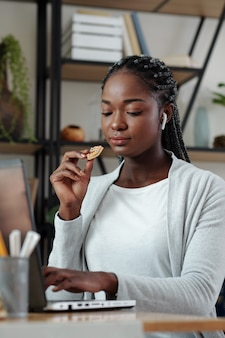 Pretty young black woman with braided hair eating homemade sugar cooke and answering e-mails on laptop
