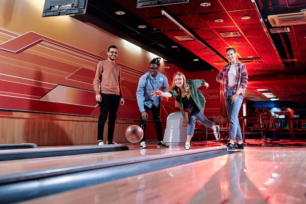 Pretty young blond female throwing bowling ball on track while standing among her intercultural friends during play