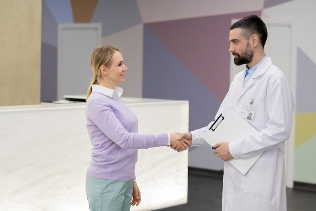 歯科医院の受付カウンターの背景に白いコートで彼女の医者の手を振るカジュアルウェアのかなり若いブロンドの女性