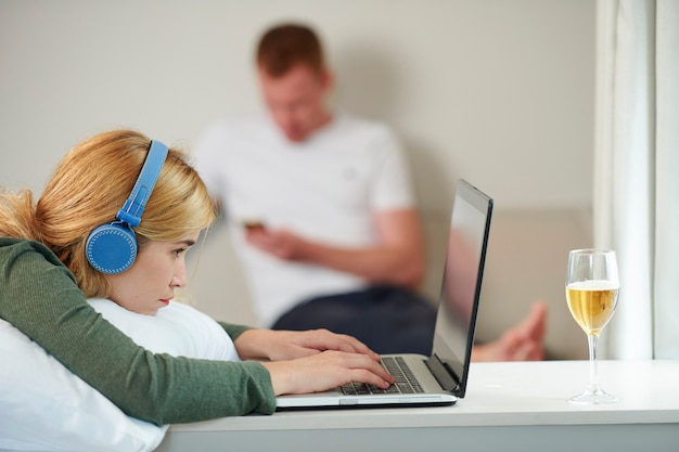 Pretty young blond woman wearing headphone when working on laptop at home