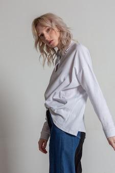 白いシャツを着て、白い背景の上のプロファイルでポーズをとってかなり若いブロンドの女性