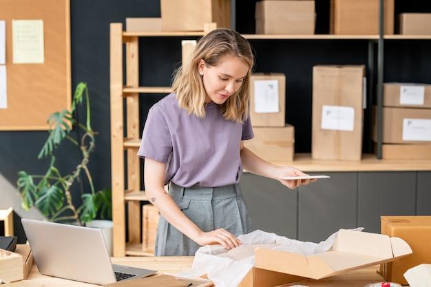Довольно молодая белокурая женщина с мобильным гаджетом стоит у стола и смотрит на сложенную зимнюю одежду в открытой коробке перед упаковкой заказа