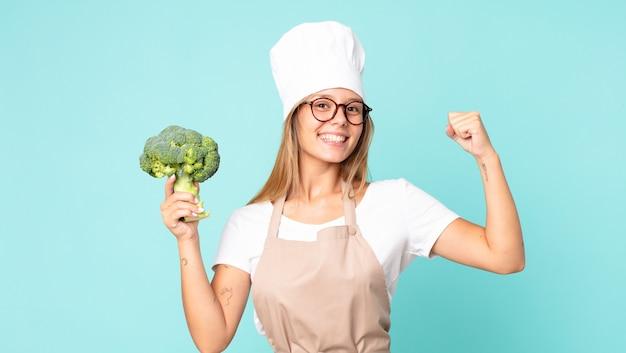 Довольно молодая блондинка повар женщина держит брокколи
