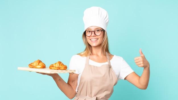 Довольно молодая блондинка повар женщина держит поднос с круассанами