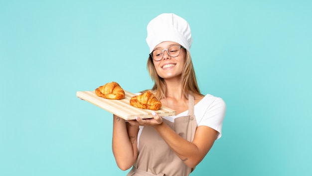 Pretty young blonde chef woman holding a croissants tray