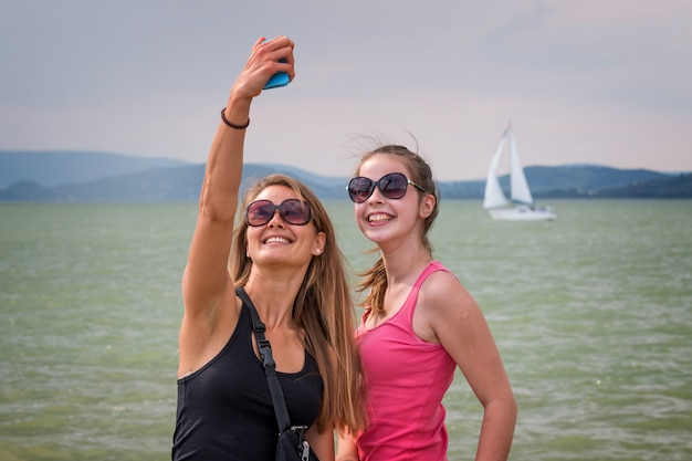 Pretty young blonde girls take a photo with mobile