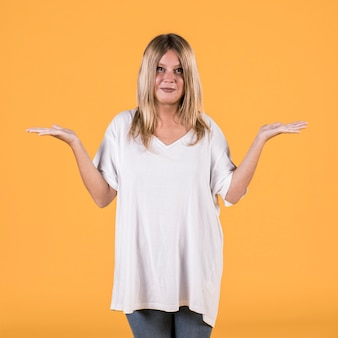 Pretty young blonde hair woman shrugging shoulders over yellow background