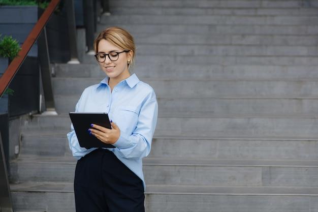 안경, 파란색 셔츠와 야외에서 서있는 동안 디지털 태블릿에서 인터넷을 서핑하는 검은 바지에 꽤 젊은 금발. 현대 가제트의 개념.