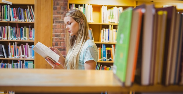 Pretty young blonde reading book in library