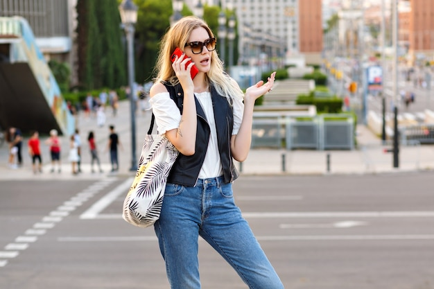 Pretty young blonde student woman speaking buy her smartphone