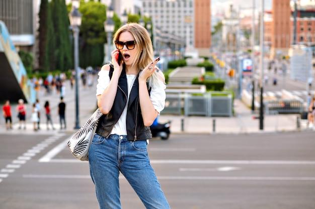 La donna bionda abbastanza giovane dell'allievo che parla compra il suo smartphone