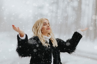 Pretty young blonde woman at snowy winter day