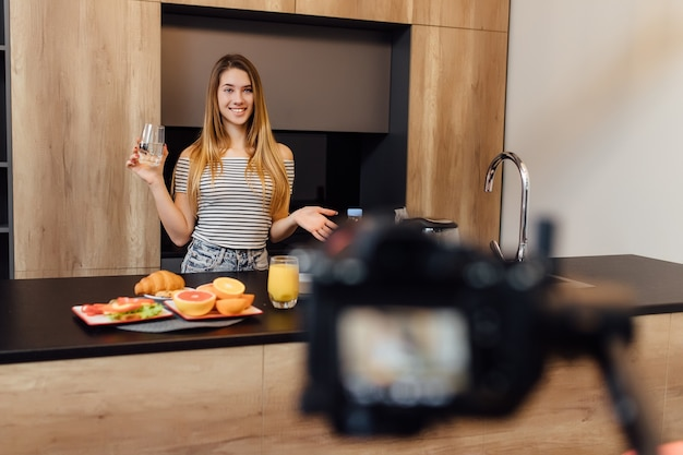 Pretty young blonde woman blogger drinking water in kitchen with healthy food on table