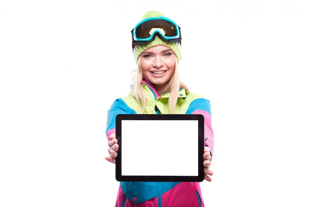 Pretty young blonde woman in colorful snow outfit show empty tablet