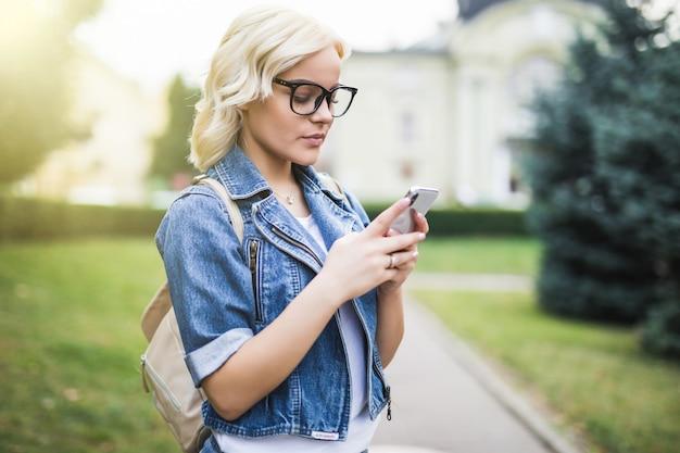 La ragazza bionda abbastanza giovane della donna utilizza il telefono per scorrere la conversazione della rete sociale nella mattina del quadrato di autunno della città