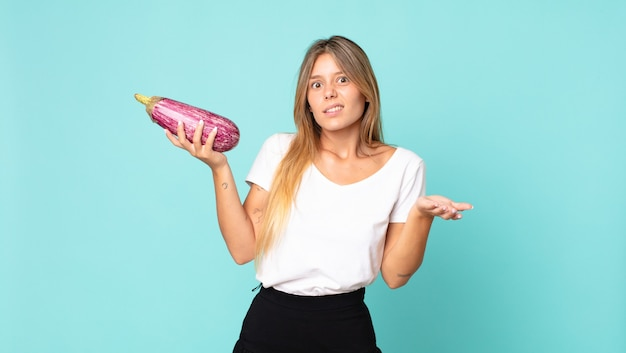 Pretty young blonde woman holding an eggplant