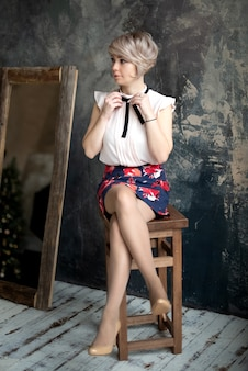 Довольно молодая блондинка сидит на стуле и завязывает бант на воротнике блузки