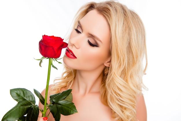 赤いバラをかぐかなり若いブロンドの女性