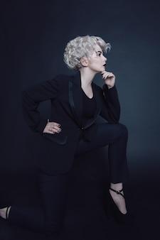 写真スタジオで黒のスタイリッシュなスーツを着て片膝で立っているかなり若いブロンドの女性