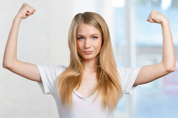 Pretty young blonde woman throwing her arms up into the air in jubilation of her success