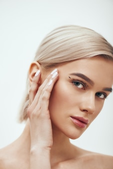 Pretty and young blonde woman touching her face with black surgical lines on eyelids and
