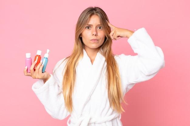 목욕 가운을 입고 화장품을 들고 있는 예쁜 금발 여성