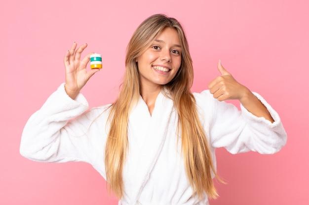 목욕 가운을 입고 화장품을 들고 있는 예쁜 젊은 금발 여성
