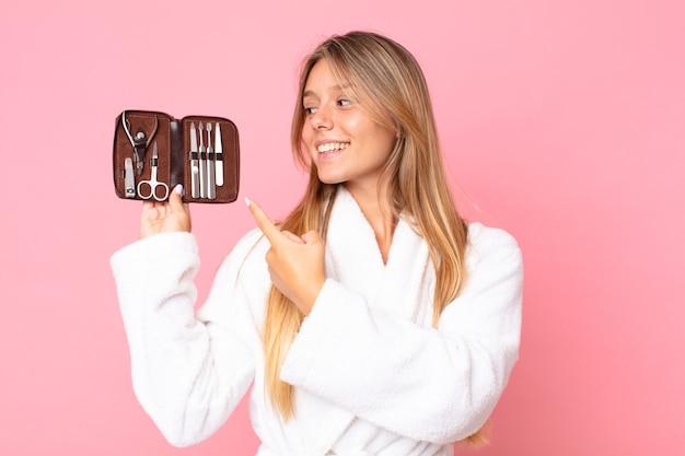 Довольно молодая блондинка женщина в халате и держит косметичку с инструментами для ногтей
