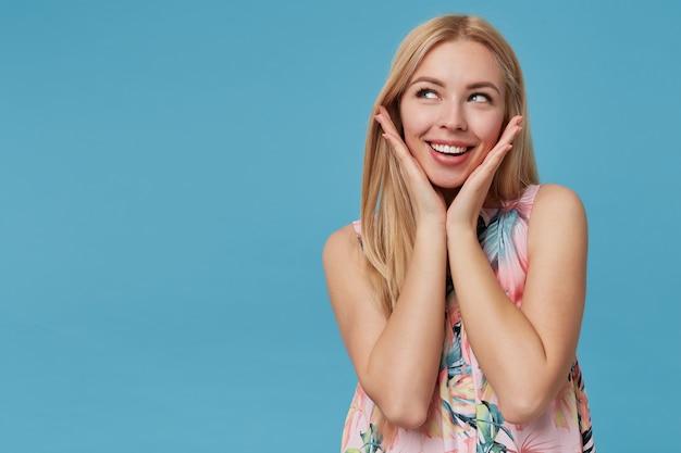 꽃 드레스를 입고 긴 머리를 가진 꽤 젊은 금발의 여자, 꿈꾸는 위쪽으로보고 행복하게 웃고, 제기 손바닥으로 격리