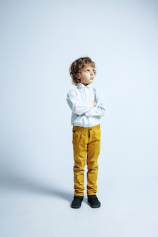 Pretty young boy in casual clothes on white studio