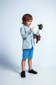 Pretty young boy in casual clothes on white wall. fashionable posing. caucasian male preschooler with bright facial emotions. childhood, having fun. talking to his teddy bear. stylish.