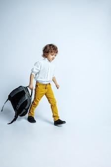 Довольно молодой мальчик в повседневной одежде на белом. модное позирование