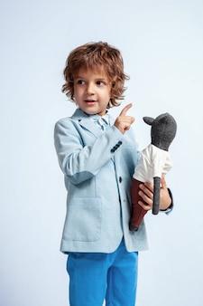 Довольно молодой мальчик в повседневной одежде на белой стене студии
