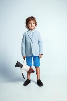 Довольно молодой мальчик в повседневной одежде на белой студии