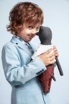 Довольно молодой мальчик в повседневной одежде на белой стене. модное позирование. кавказский дошкольник мужского пола с яркими эмоциями на лице. детство, веселье. обнимается со своим плюшевым мишкой. стильно.