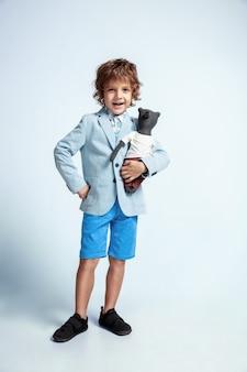 흰 벽에 캐주얼 옷에 꽤 어린 소년. 유행 포즈. 밝은 얼굴 감정을 가진 백인 남성 미취학 아동. 어린 시절, 재미. 그의 테디 베어와 포옹. 세련된.