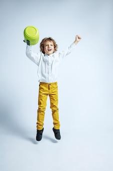 Довольно молодой мальчик в повседневной одежде на белой стене