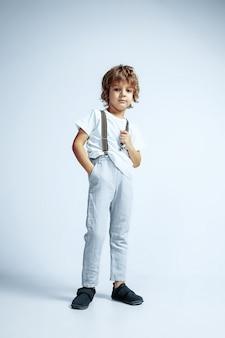 Довольно молодой мальчик в повседневной одежде на белом